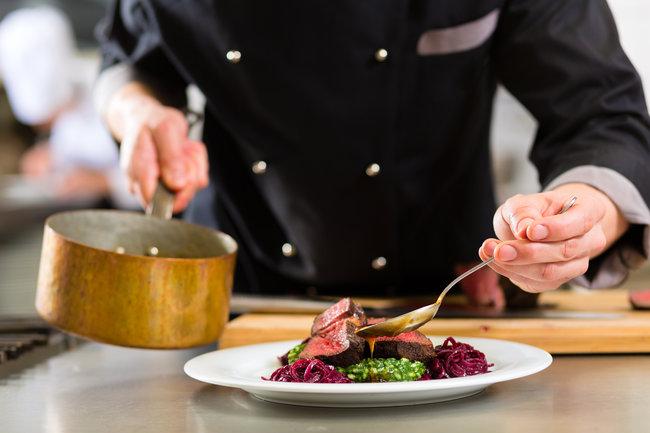 Chef spooning gravy onto meat